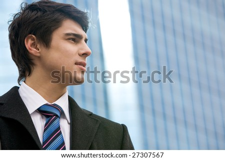 Pensive businessman looking into the distance somewhere outdoors - stock photo