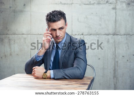 Pensive businessman sitting at the table and talking on the phone over concrete wall. Looking away - stock photo