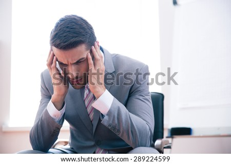 Pensive businessman sitting on office chair in office - stock photo
