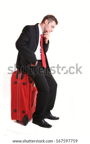 Pensive businessman sitting on red luggage isolated on white