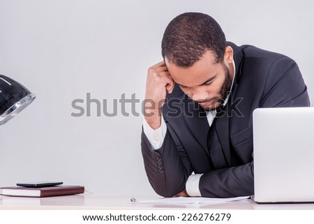 Pensive businessman. Smiling African businessman sitting at the table and typing a business plan on laptop while businessman sitting at the table and thinking on the table on isolated gray background