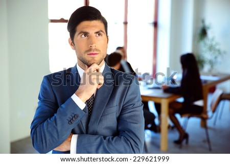 Pensive businessman standing in front of colleagues - stock photo