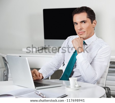 Pensive businessman working with laptop at his desk in the office - stock photo