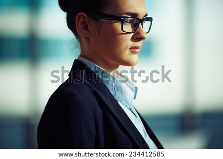 Pensive businesswoman in eyeglasses and formalwear - stock photo