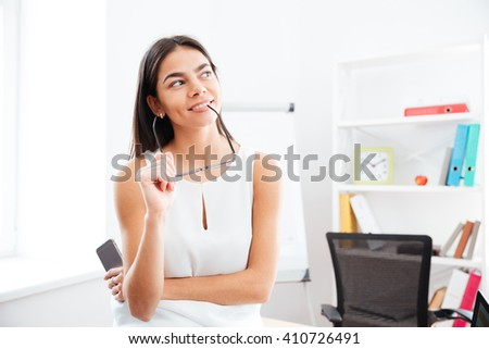 Pensive businesswoman looking away in office - stock photo