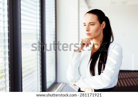 Pensive businesswoman looking from the window
