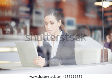 Pensive businesswoman reading an article on tablet computer in a bar - stock photo