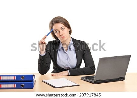 Pensive businesswoman sitting at a desk isolated on white background - stock photo