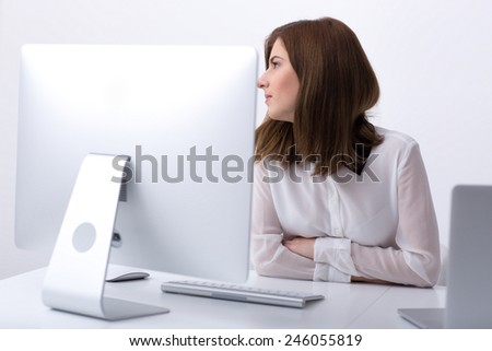 Pensive businesswoman sitting at her workplace in office