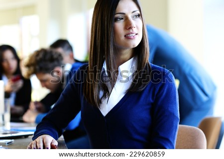 Pensive businesswoman sitting at the table with colleagues on background - stock photo
