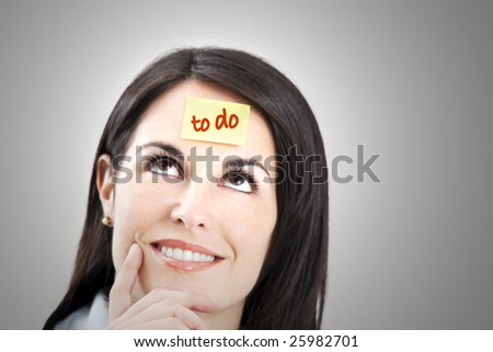 pensive businesswoman with blank adhesive note on forehead. Copy space - stock photo