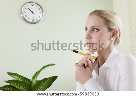 Pensive businesswoman with pen