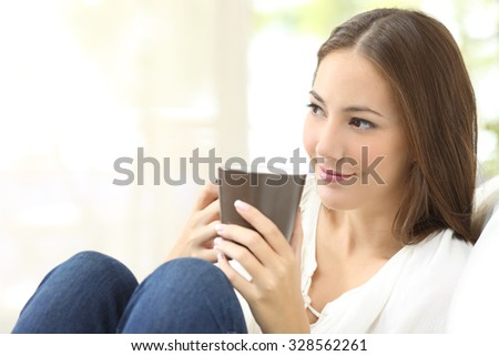 Pensive candid girl looking sideways and holding a coffee cup sitting on a couch at home - stock photo