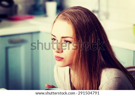Pensive caucasian woman in the kitchen - stock photo