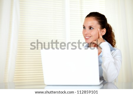 Pensive caucasian young woman looking right in front of her laptop - copyspace - stock photo