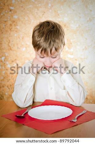pensive child looks at the empty plate