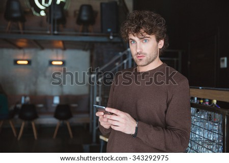 Pensive curly young daydreaming thoughtful handsome man holding mobile phone and using it in cafe - stock photo