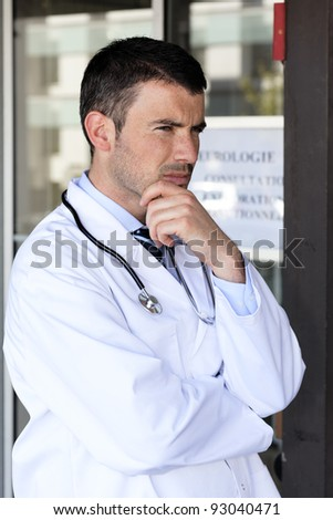 pensive doctor with stethoscope in front of hospital - stock photo
