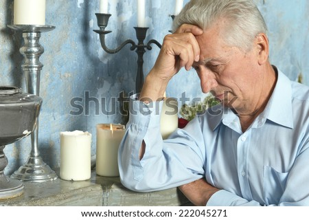 Pensive elderly man sitting on the table - stock photo