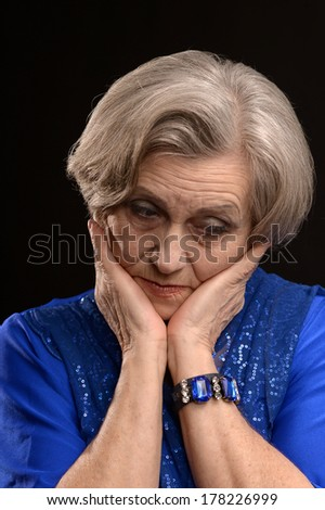 Pensive elderly woman on a black background