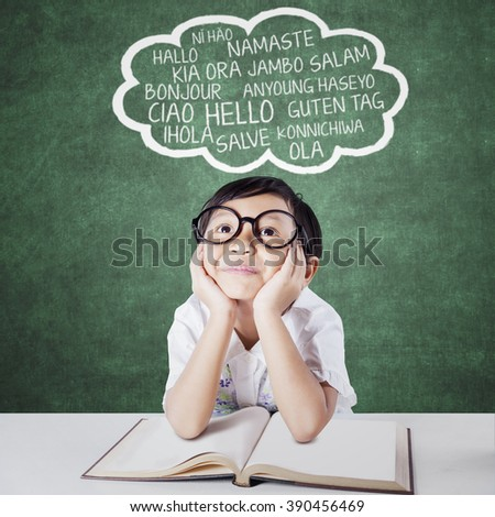 Pensive elementary school student imagine multi language while studying with a textbook in class