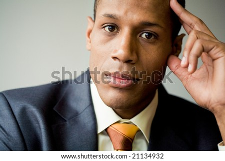Pensive employee thinking of new ideas and looking at camera - stock photo
