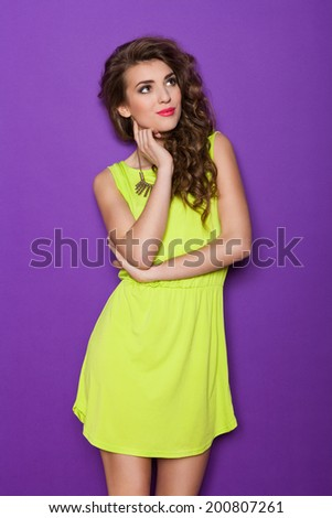 Pensive fashionable girl. Summer girl in lime green mini dress thinking and looking up. Three quarter length studio shot on violet background. - stock photo