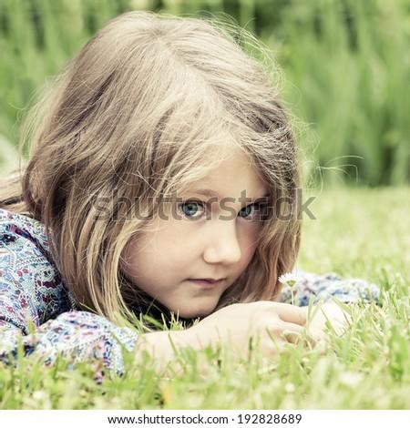 Pensive girl lying on grass  - stock photo