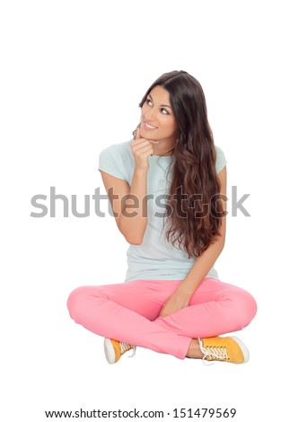 Pensive girl sitting on the floor isolated on white background - stock photo