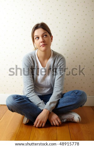 Pensive girl sitting on the floor of the room - stock photo