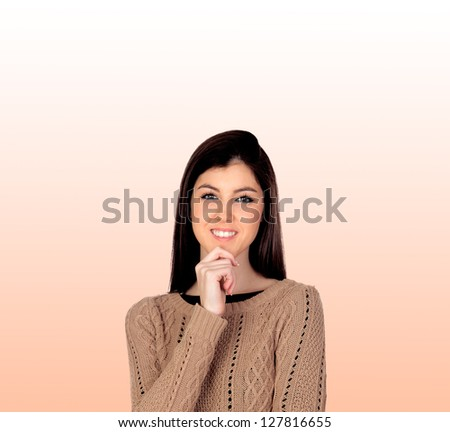 Pensive girl smiling isolated on a orange background - stock photo