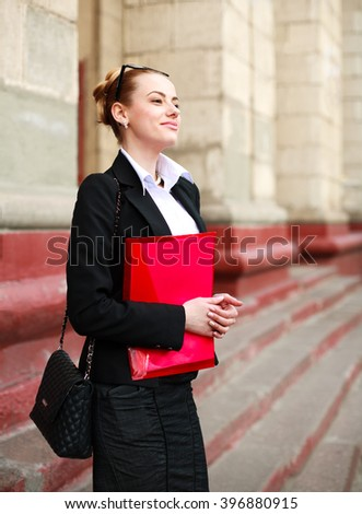 Pensive girl student with a folder of documents in front of the university building - stock photo