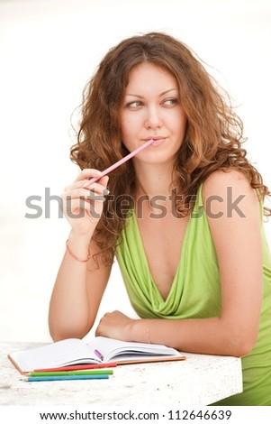 Pensive girl writes a letter - stock photo
