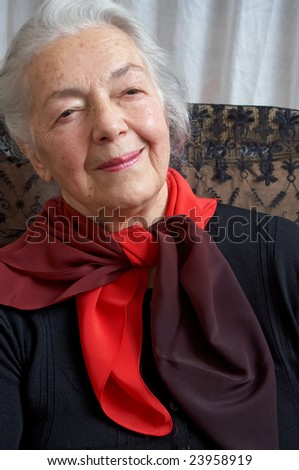 Pensive grandmother with red scarf - stock photo