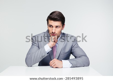 Pensive handsome businessman sitting at the table over gray background