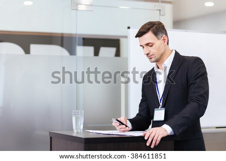 Pensive handsome speaker using mobile phone standing at the tribune in conference hall - stock photo