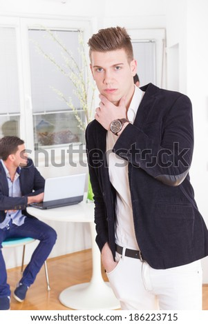 pensive handsome successful business man with colleague in background using laptop - stock photo