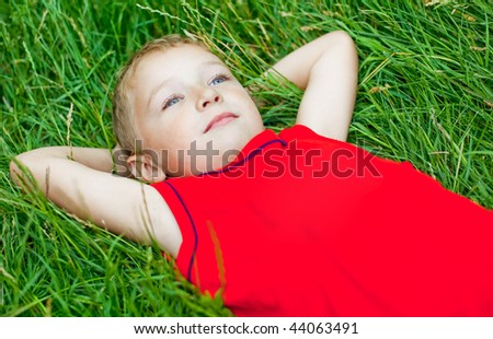 Pensive kid day dreaming in fresh grass