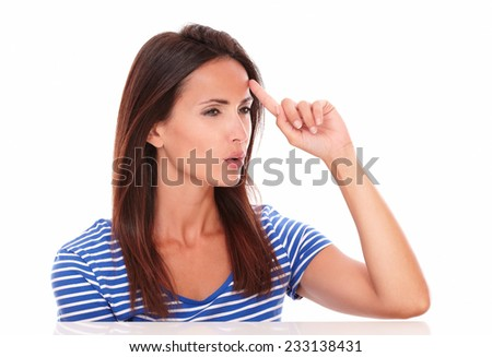 Pensive lady looking to her left and pointing to her forehead in white background - copyspace