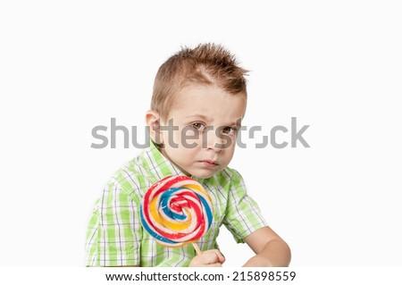 Pensive little boy con lollipop  - stock photo