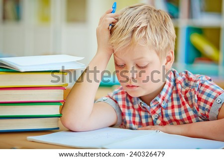 Pensive little boy looking at page of his copybook at lesson - stock photo