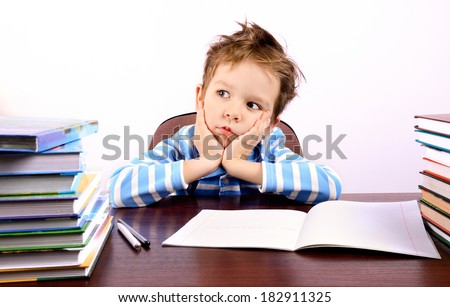 Pensive little boy sitting at a desk. on the table are many books and a notebook. ruffled the boy's hair. he holds his head. on a light background. horizontal - stock photo