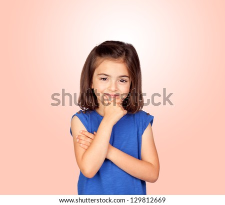 Pensive little girl isolated on a over orange background - stock photo