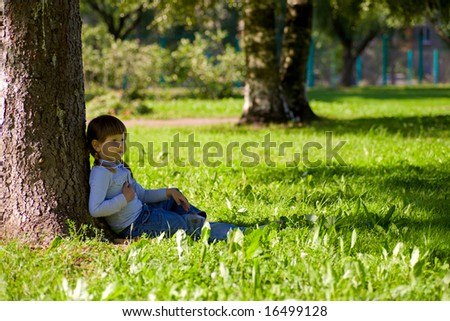 Pensive little girl sitting in the grass near tree - stock photo