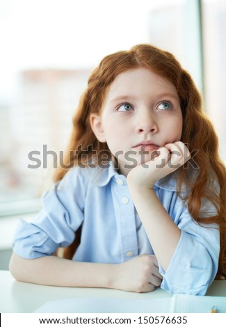 Pensive little girl touching her cheek and thinking about something - stock photo