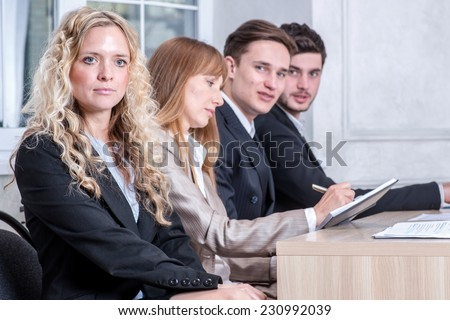 Pensive look. Serious businessman looking ahead while his colleague businessmen talking in the background - stock photo