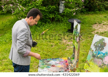 Pensive male artist holding a professional paintbrush and choosing colors on the colorful palette of blended oil paints outdoors with background of beautiful bushes - stock photo