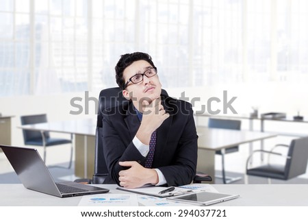 Pensive male entrepreneur working with laptop while thinking idea and looking up with hand on his chin, shot in the office - stock photo