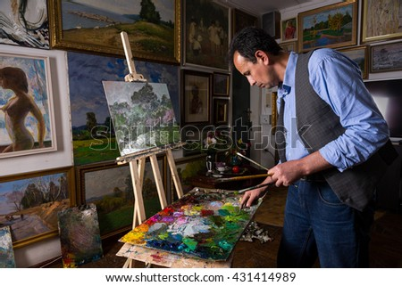 Pensive male painter holding professional paintbrushes and mixing paint by paletteknife on the colorful palette of blended paints in a studio with background of original artworks hanging on the wall