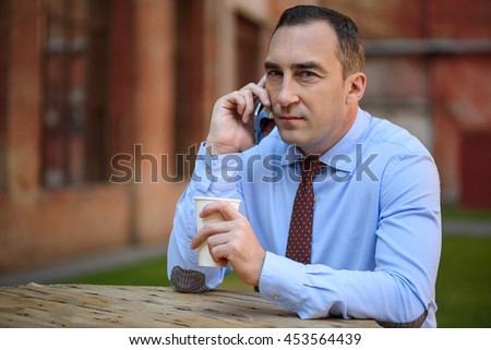 Pensive male worker using telephone for communication - stock photo